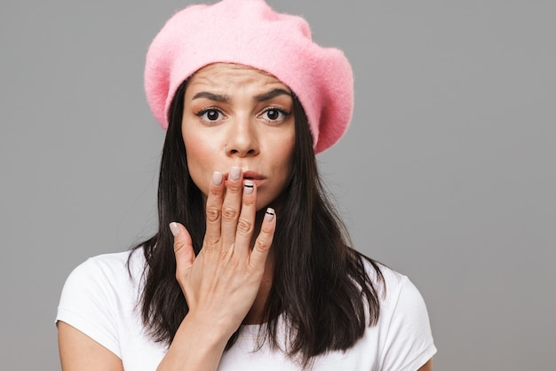 Portret close-up van verwarde mooie vrouw in basic t-shirt en baret camera kijken en bedekken haar mond met hand geïsoleerd over grijze muur