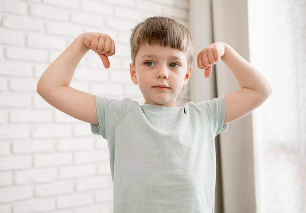 Portret dat van aanbiddelijke jongen zijn spieren toont