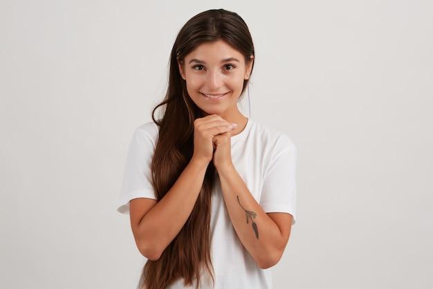 Portret dat van aantrekkelijk, volwassen meisje met donker lang haar, wit t-shirt draagt