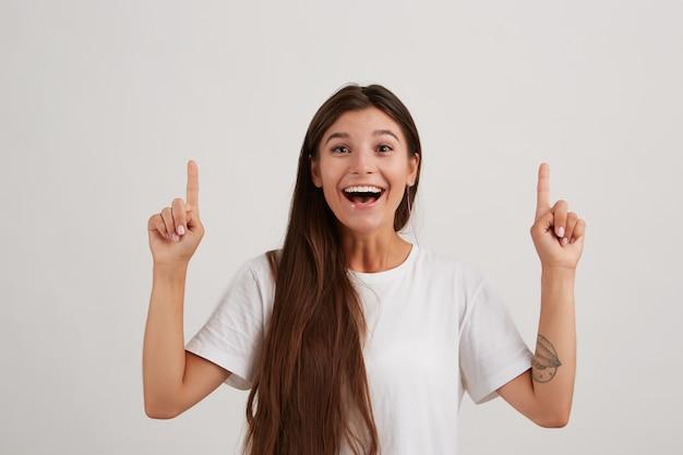 Portret dat van aantrekkelijk, vrolijk meisje met donker lang haar, wit t-shirt draagt