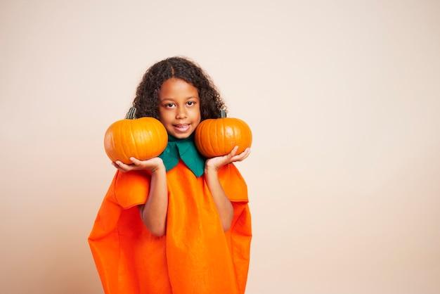 Portret dat van afrikaans meisje twee halloween-pompoenen houdt