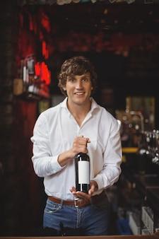 Portret dat van barman een fles wijn houdt