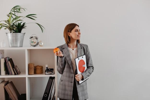 Portret dat van bedrijfsvrouw met cirkeldiagram in haar handen aan kant kijkt. de glimlachende vrouw gaat appel eten voor lunch in bureau.