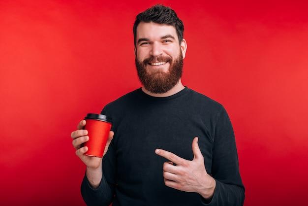 Portret dat van de gelukkige mens zich over rode ruimte bevindt en op kop van koffie richt om te gaan