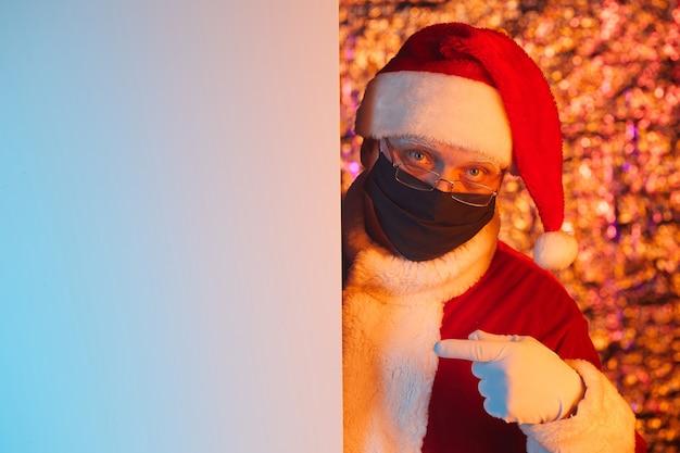 Portret dat van de kerstman in beschermend masker op lege affiche richt die hij iets aanbeveelt