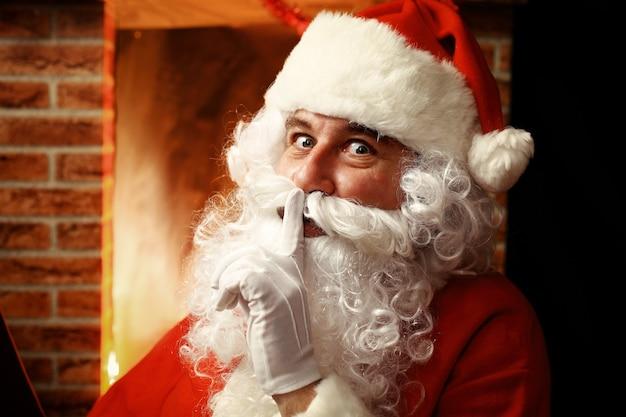 Portret dat van de kerstman wijsvinger door zijn mond houdt