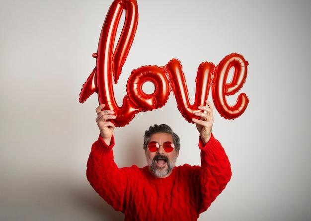 Portret dat van de mens een ballon in de vorm van het woordliefde op witte achtergrond houdt. valentijnsdag viering