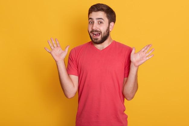 Portret dat van de mens wordt verrast, knap mannetje dat zijn handen uitspreidt, geïsoleerd stellen over gele muur, aantrekkelijke ongeschoren kerel die rode toevallige t-shirt draagt. het concept van menselijke emoties.