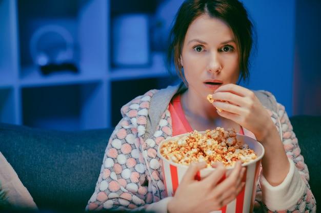 Portret dat van de vrouw is ontsproten die met popcorn op de bank zit lettend op iets eng terwijl het eten van popcorn en bang is