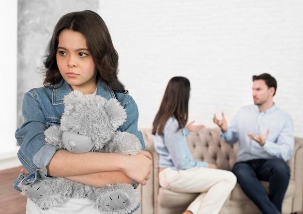 Portret dat van droevig kind haar teddybeer houdt