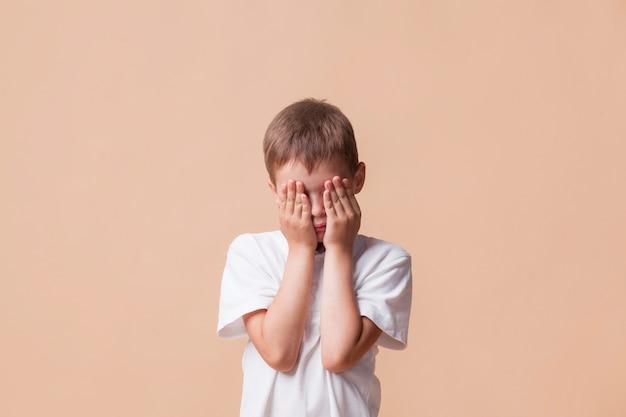 Portret dat van droevige jongen zijn gezicht behandelt met hand