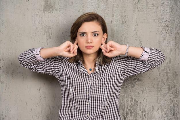 Portret dat van een jonge vrouw met handen haar oren behandelt
