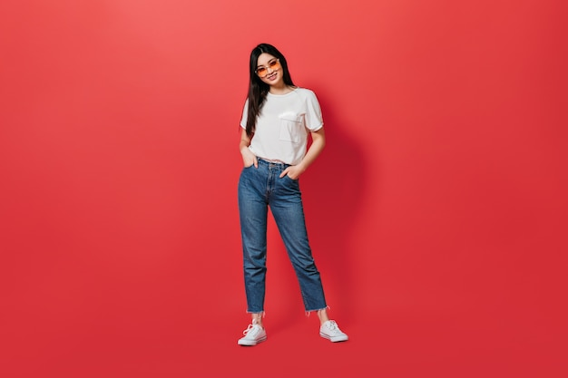 Portret dat van een vrouw in volle groei, wit t-shirt en spijkerbroek draagt