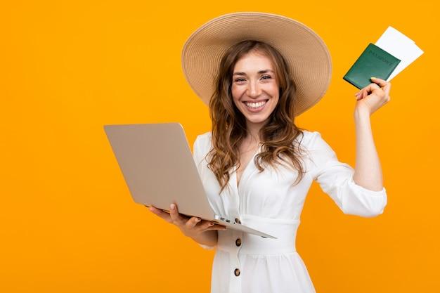 Portret dat van emotioneel meisje, laptop en een paspoort met kaartjes houdt
