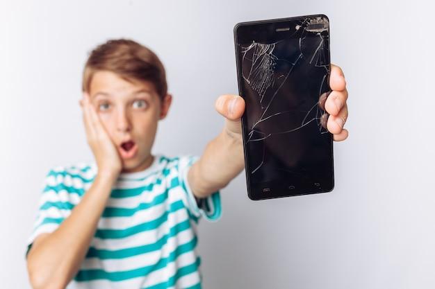Portret dat van emotionele jongen gebroken mobiele telefoon toont