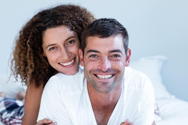 Portret dat van gelukkig paar op bed ligt