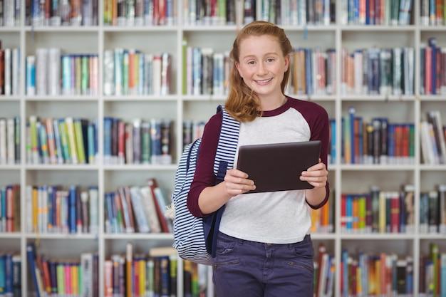 Portret dat van gelukkig schoolmeisje digitale tablet in bibliotheek houdt