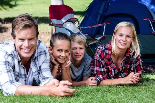 Portret dat van gelukkige familie op gras ligt