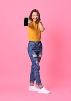 Portret dat van gelukkige jonge vrouw bij lege het scherm mobiele telefoon over roze toont.