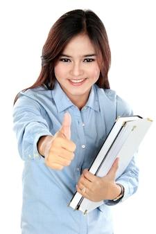 Portret dat van gelukkige student een paar boeken en duimen tegenhoudt
