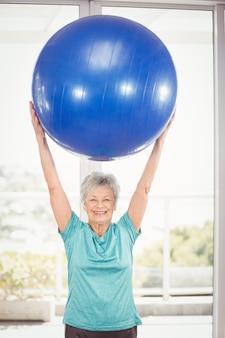 Portret dat van gelukkige vrouw blauwe oefeningsbal houdt
