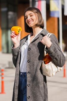 Portret dat van gelukkige vrouw ecologische groenten houdt