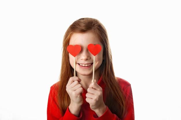 Portret dat van glimlachend roodharig meisje haar ogen behandelt met rode harten op stokken