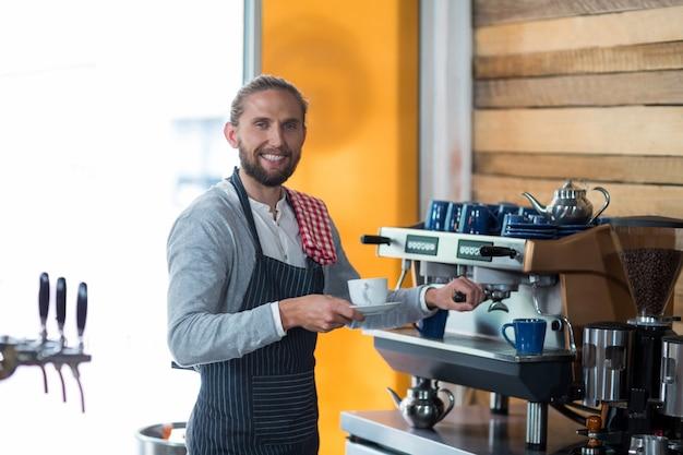 Portret dat van glimlachende kelner kop van koffie maakt