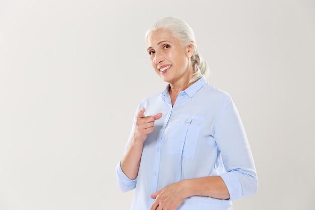 Portret dat van glimlachende oude vrouw met vinger aan u richt
