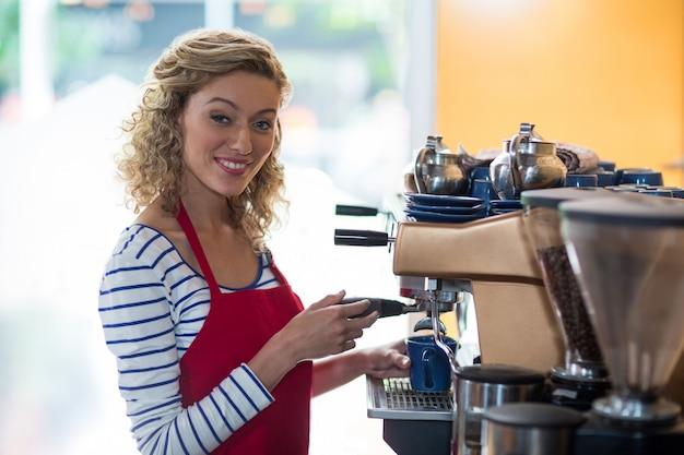 Portret dat van glimlachende serveerster kop van koffie maakt