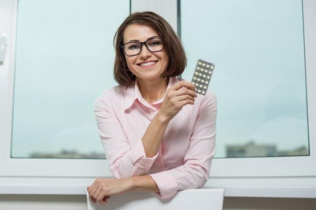 Portret dat van glimlachende vrouw een pil houdt
