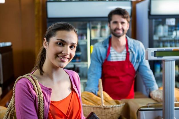 Portret dat van glimlachende vrouw zich dichtbij betalingsteller bevindt