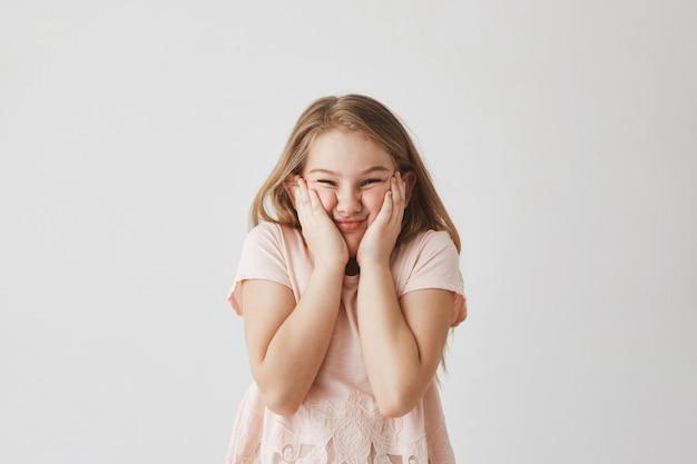 Portret dat van grappig blondemeisje in roze kleding gezicht met handen drukt, dwaze gezichten maakt die verhindert dat moeder goede foto van haar neemt.