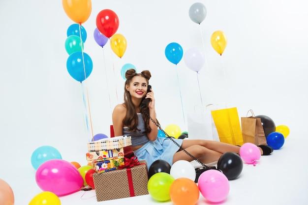 Portret dat van grappig meisje telefoongesprekzitting op vloer neemt