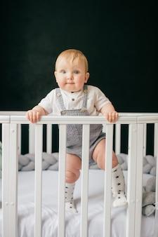Portret dat van grappige baby zich in voederbak bevindt.