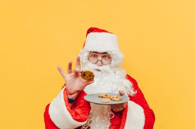 Portret dat van grappige kerstman een plaat met koekjes houdt