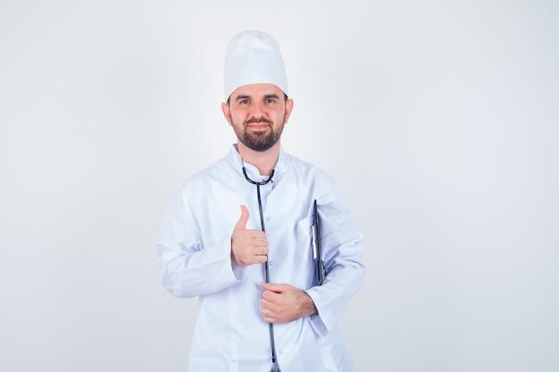 Portret dat van het jonge mannelijke klembord van de artsenholding, duim in wit uniform toont en vrolijk vooraanzicht kijkt