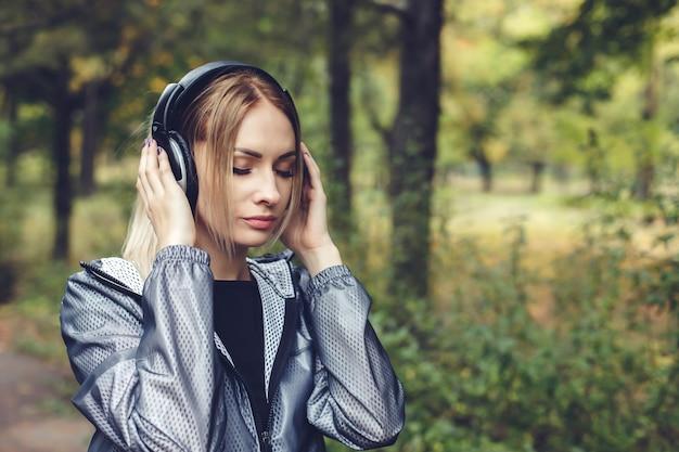 Portret dat van jong aantrekkelijk blondemeisje op een stadspark, aan muziek op hoofdtelefoons luistert