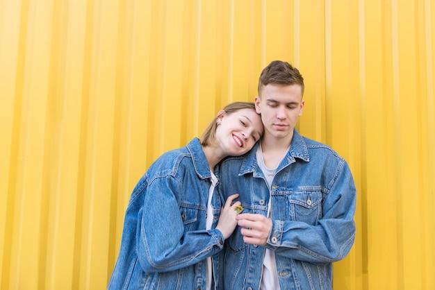 Portret dat van jong paar zich op achtergrond van gele muur en het glimlachen bevindt