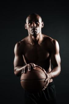 Portret dat van jonge afro-amerikaanse basketbalspeler, bal voorbereidingen treft te werpen