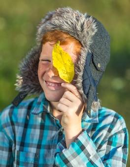 Portret dat van jonge jongen een geel verlof houdt