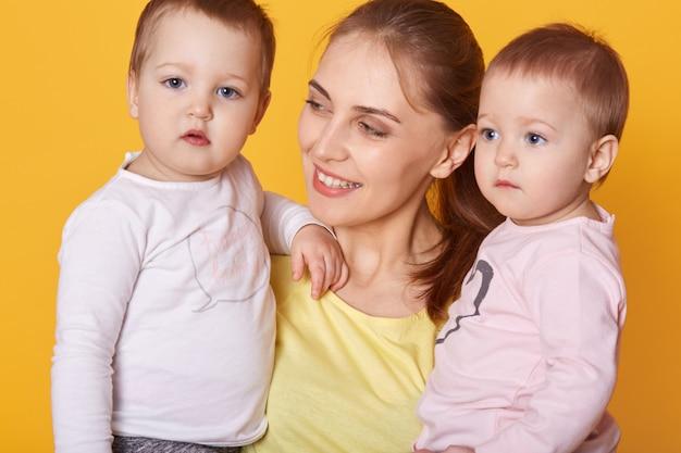 Portret dat van jonge moeder haar kleine tweelingen houdt