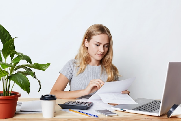 Portret dat van jonge onderneemster die met laptop en calculator werkt, aandachtig documenten bekijkt, rekeningen van bedrijf berekent, die financieel verslag maakt. mensen, carrière en bedrijfsconcept