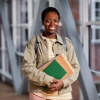 Portret dat van jonge student een bos van notitieboekjes houdt