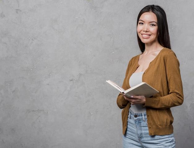 Portret dat van jonge vrouw een boek houdt