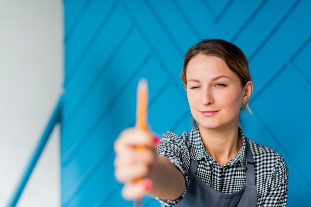 Portret dat van jonge vrouw een potlood houdt