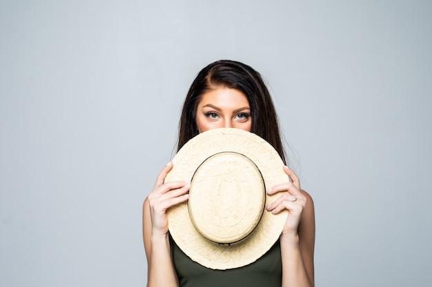 Portret dat van jonge vrouw haar gezicht behandelt met geïsoleerde de zomerhoed.