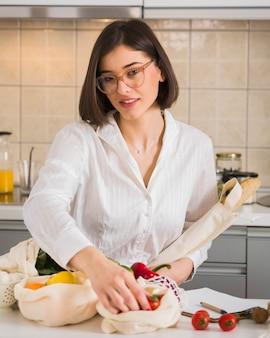Portret dat van jonge vrouw kruidenierswinkels neemt uit zakken