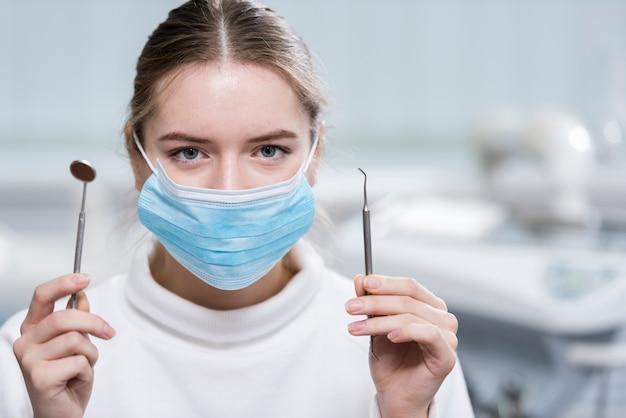 Portret dat van jonge vrouw medische hulpmiddelen houdt