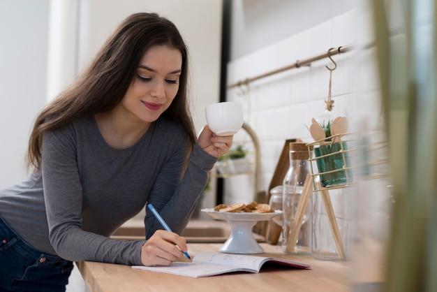Portret dat van jonge vrouw nota's neemt terwijl het hebben van koffie